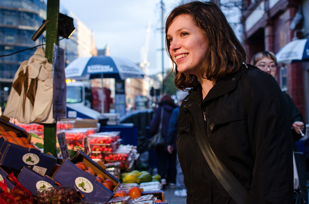 A lady shopping at a fruit and veg stall in a market
