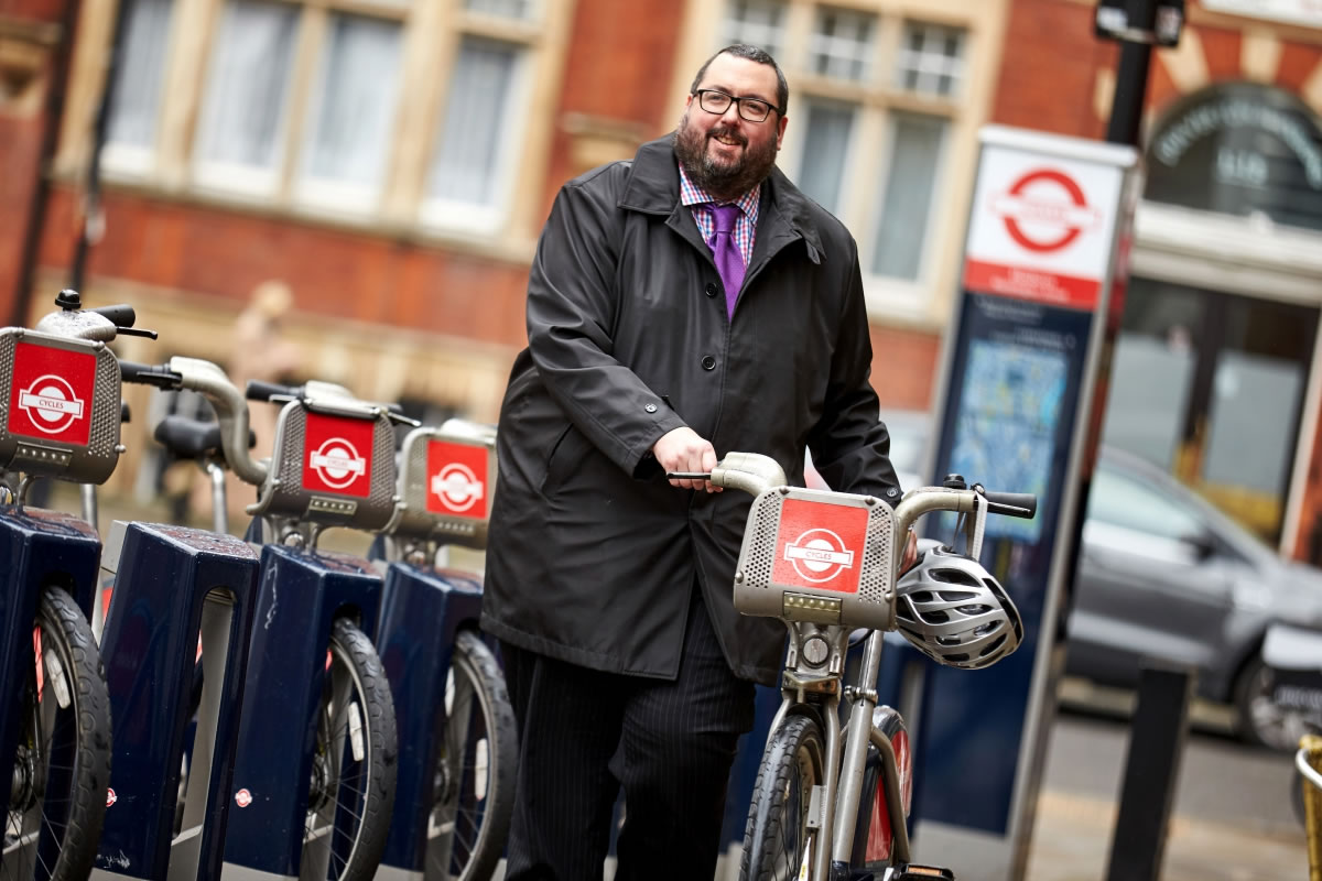 A man with a bicycle on a London street