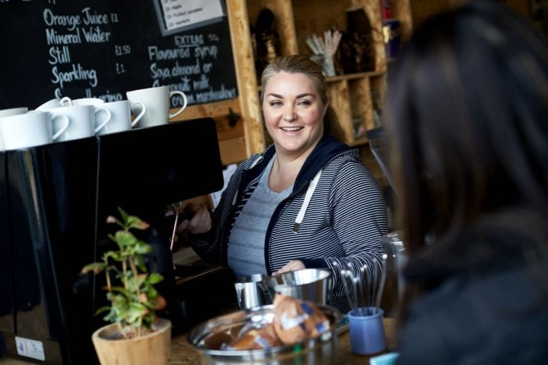 A female barista serves a customer a coffee