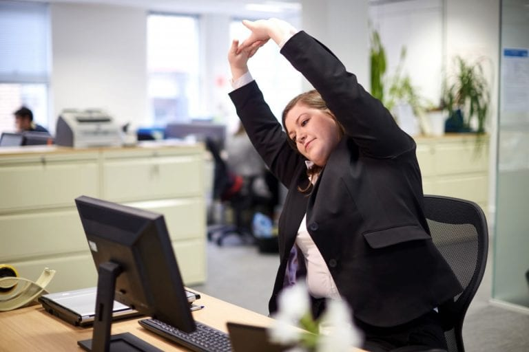 A female office worker stretches whilst sitting at her desk