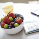 Bowl of fruit alongside a newspaper